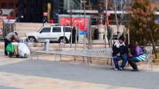 An overweight couple sit at one end of a bench while a homeless person searches the bin at the other