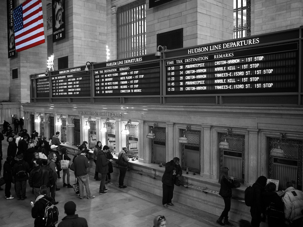 Black and white photo showing people queuing at counters beneath departure boards in Grand Central