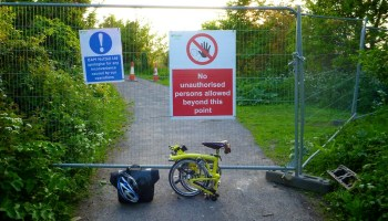 Folding Brompton bike in front of a construction fence