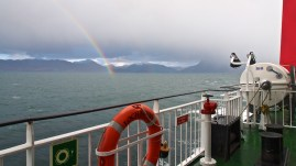 Over-the-railings view from a ferry of a rainbow as it disappears into a murky loch beneath threatening clouds, mountains on the horizon