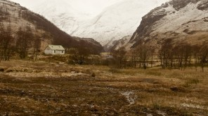 Aged picture of a lonely hut in a glen in front of a mountain range