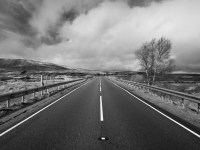 Black and white photo from the centre of a long, straight road as it snakes off towards the horizon