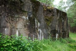 Side-on view of a thick wall that's pock-marked by ancient heavy artillery