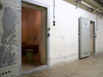View from a corridor into a primitive cell, interior shows a wooden bed and metal bucket