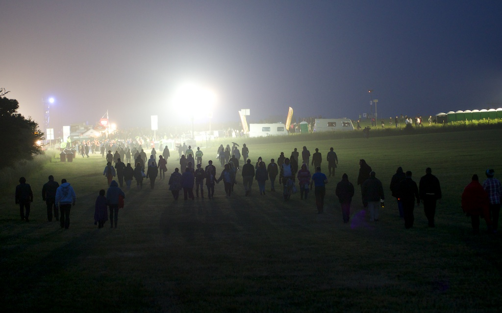 Long shot of silhouetted people walking across a field at night toward a light rig