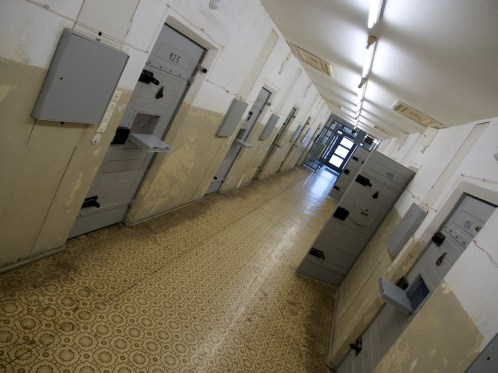 Angled image looking down a prison corridor, some cell doors are open