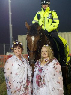 Two ladies are having their photo taken in front of a police horse, its female ride smiling