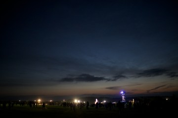 The night sky above electric light towers and crowd near the stones