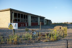 A sign warns visitors not to approach some trashed single storey buildings