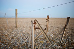The remains of a wire fence are slowly being reclaimed by the surrounding shingle
