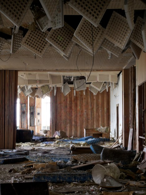 Ceiling tiles hang down into a derelict, vandalised room