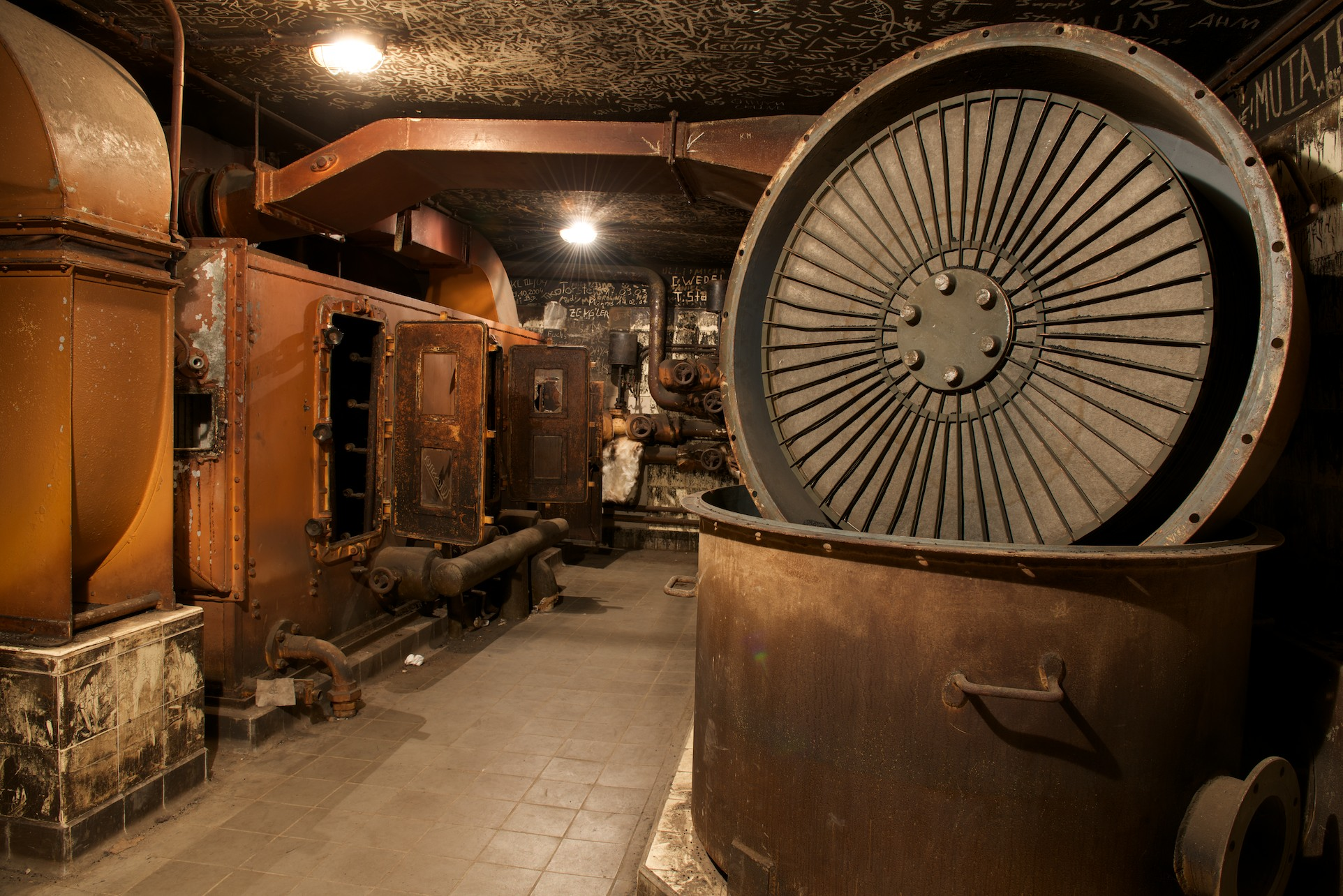 What looks like a large kettle stands in front of an old oven in a room which has undergone an intense fire
