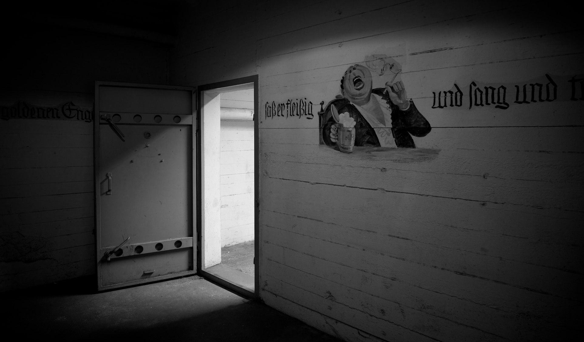 Black and white image of light coming into a cellar through a thick steel door, illuminating an illustration of Wilhelm Busch character Hieronymus with beer mug