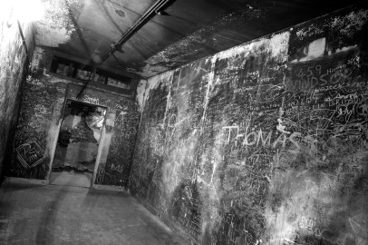 An empty windowless room whose walls are covered with graffiti, scratched into thick black soot