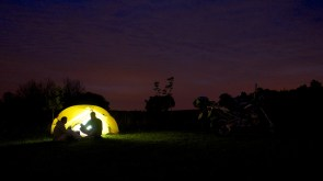 Silhouette of two campers in front of lit up tent, bikes to one side.