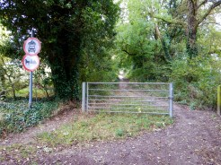 A metal gate and signs bar the road to bikes, cars, and horse traps