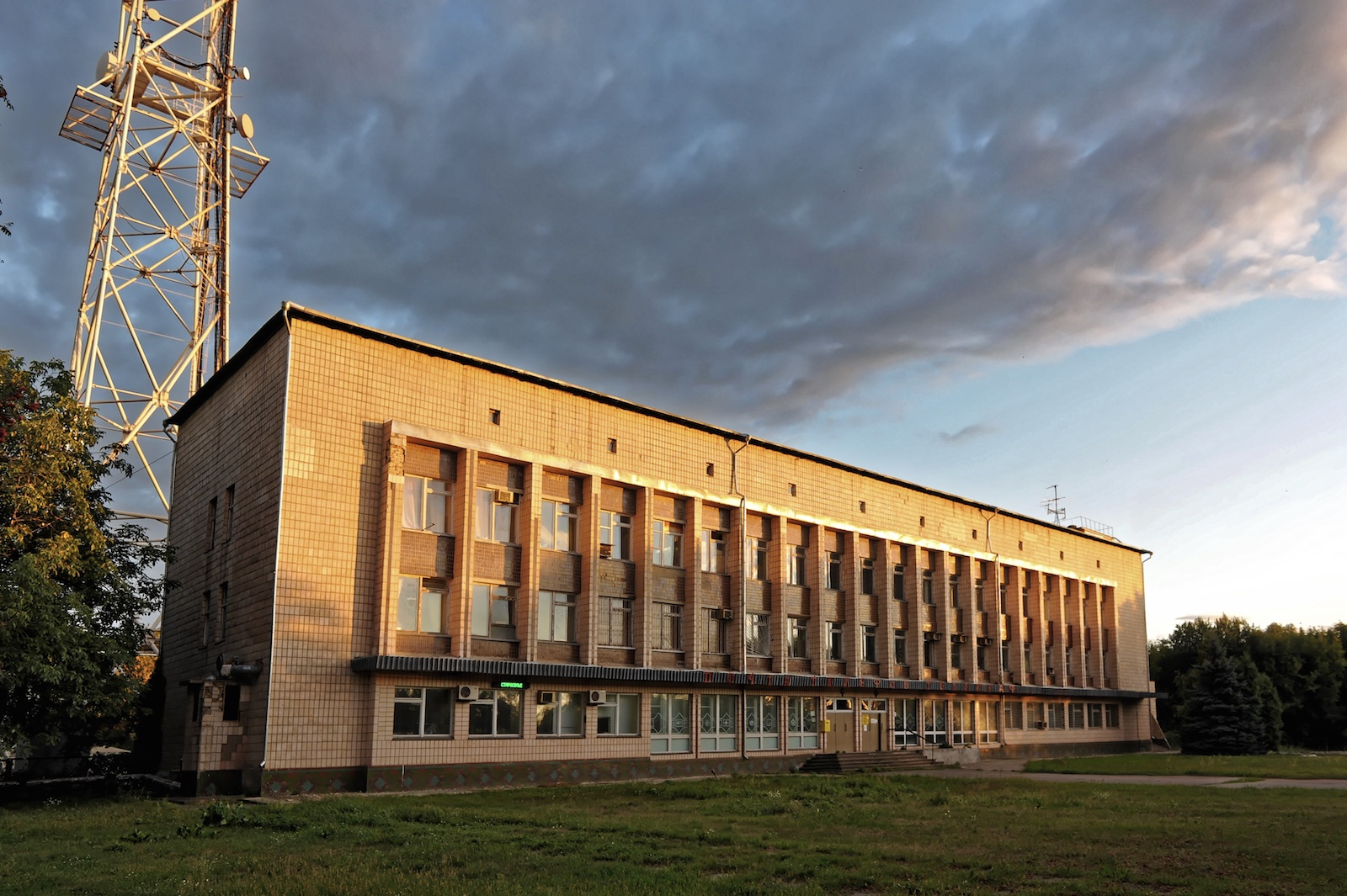 Clouds gather above an imposing 4 storey concrete building next to a transmission antenna. A small LED dot matrix board is just visible near one corner at floor level.