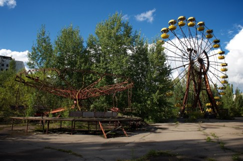 Pripyat's famous ferris wheel behind a large bush which appears to be growing out of a merry-go-round