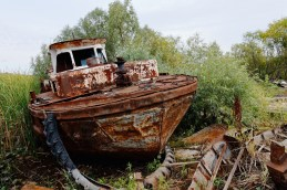 A rusty boat has been pulled out of the weeds at the edge of a river
