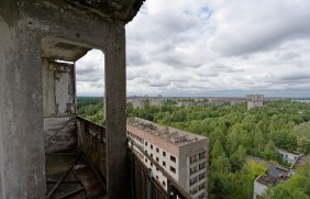 View from a tower block balcony far across an overgrown city, reactor 4 just visible on the horizon.