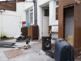 A suitcase and an old speaker are among the clutter adorning a derelict conservatory