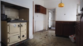 Interior photo of an abandoned kitchen, old fashioned range to the left