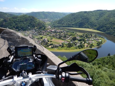 Bike parked against concrete barrier far above a town in the neck of a river
