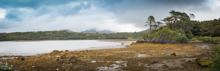 Improbable panorama includes small pieces of blue sky above wide bay, small islet covered in trees and statue of Virgin Mary.
