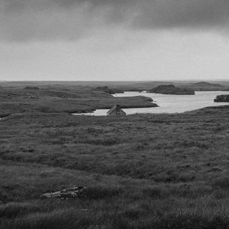 Roof of small fishing hut just visible among wide monochrome panorama of peatland around irregular shaped lake