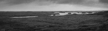 Roof of small fishing hut just visible among wide monochrome panorama of peatland around irregular shaped lake