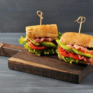 Appetizing sandwich on a wooden board. Baguette sandwich with filling from lettuce, slices of fried bacon, tomato and avocado. Dark wooden b