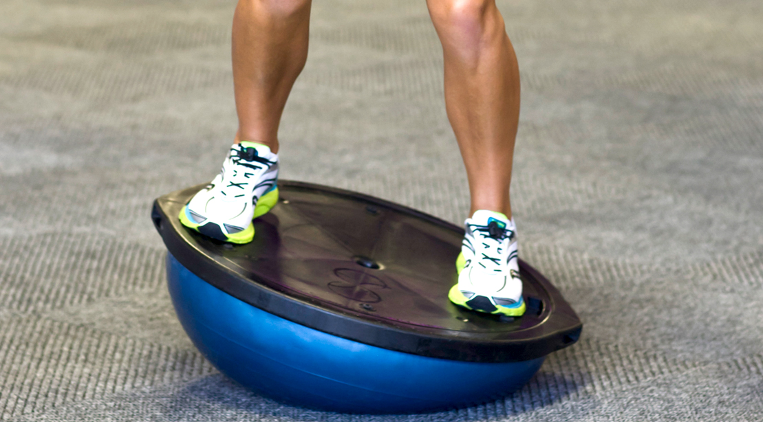 Man working out with a Bosu ball tilting and training with instability