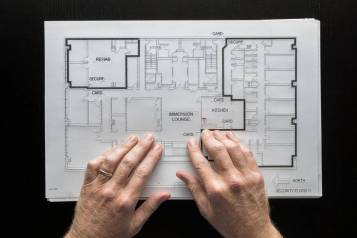 Two hands touching a floor plan