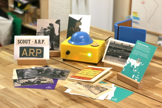 The finish scouts collections, including two sets of postcards, a replica 'Point-It-Out' book, a 3D print of a ARP warden's helmet and a 3D printed replica of a wooden hand-carved logbook.