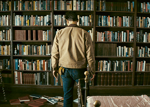 Matthew McConaughey stands in front of the bookcase in 'Interstellar'