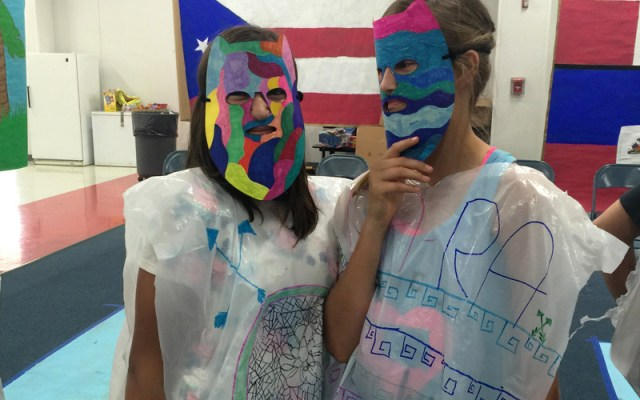 Two girls from Explorer's camp don paper masks.