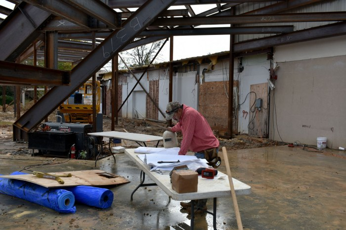 A contractor checks the building plans before placing decking sheets on the roof of the Museum's new lobby (November, 2017).