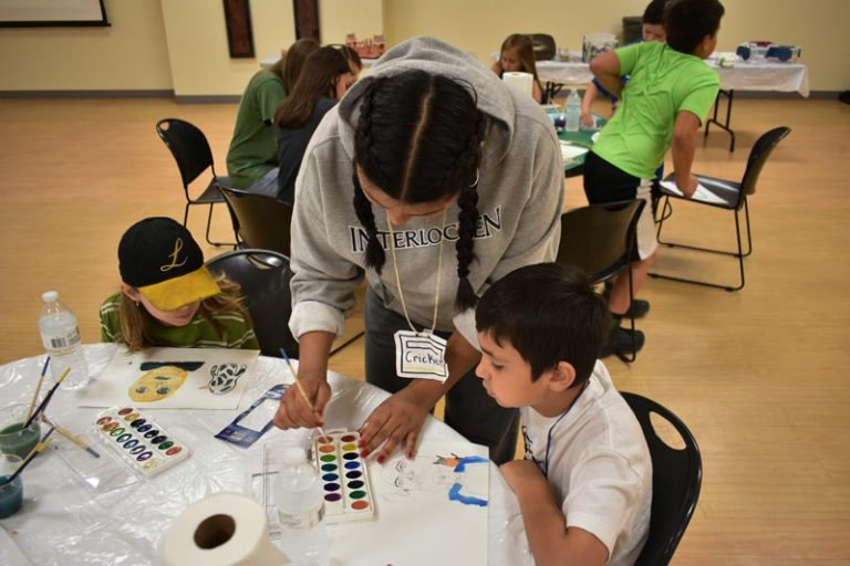An explorer's camp counselor leading an art class