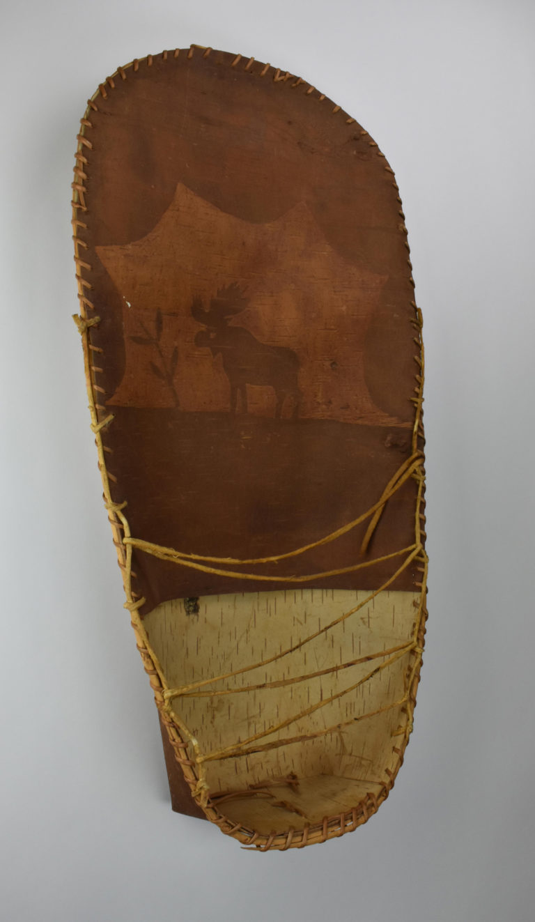 A small, birch bark cradle decorated with an image of a moose