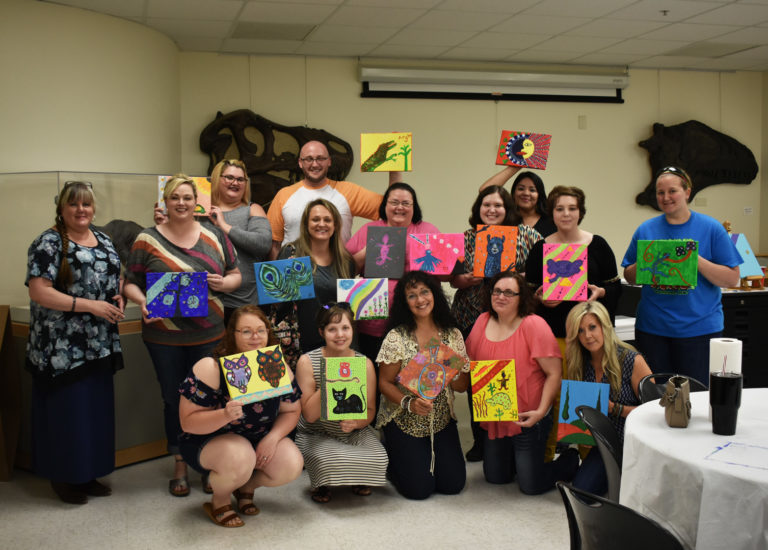 A group of adults holding a various paintings they created
