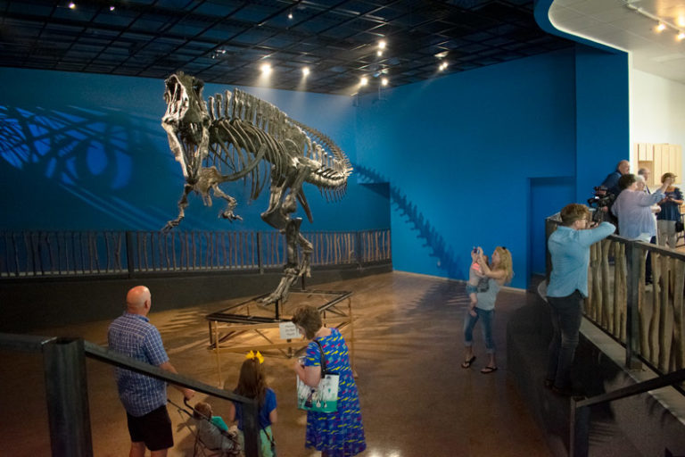 A family taking pictures of the Oklahoma State Dinosaur, Acrocanthosaurus atokensis