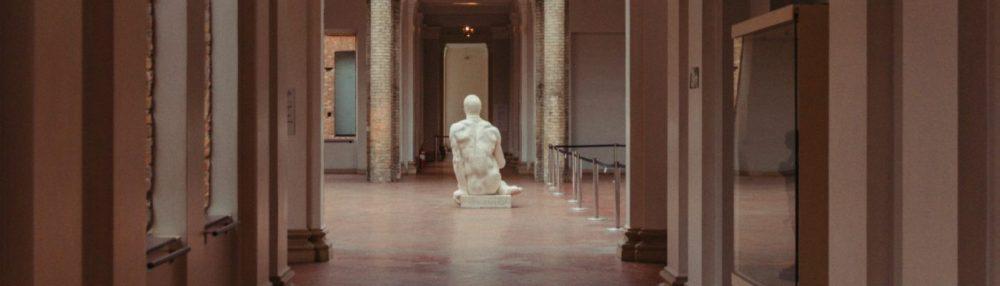 Couloir vide du musée avec une statue de marbre à la fin