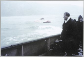Man on the deck of the TEV Wahine looks out on two red liferafts and a lifeboat