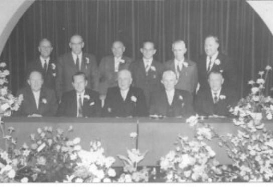 Het bestuur van woningbouwvereniging Zuilen kijkt u stralend aan. De tweede persoon links is de heer Smit.