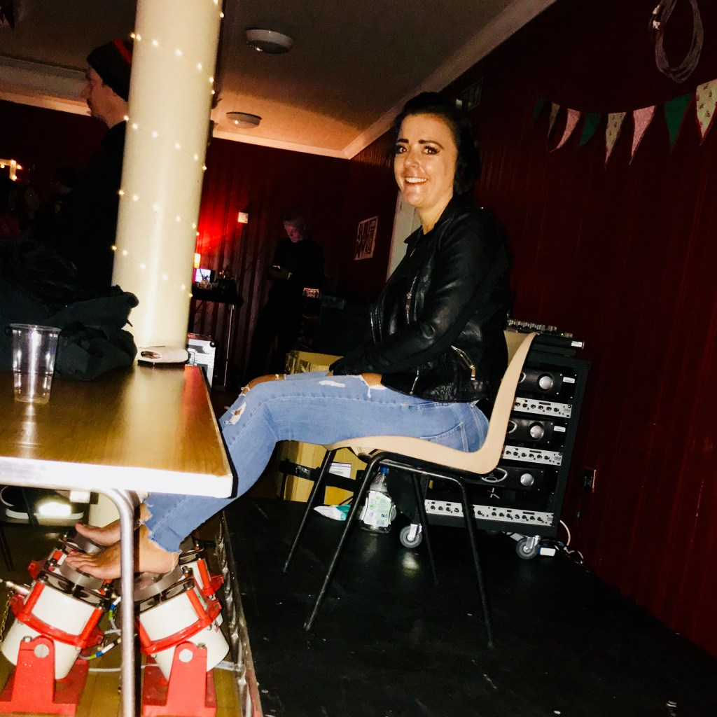 Woman in leather jacket and blue jeans seated with bare feet using four vibrotactile shakers at a live music event