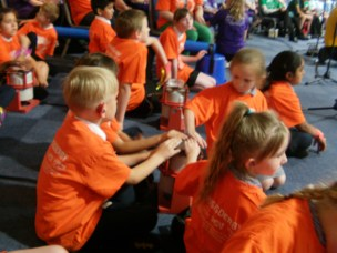 Young school pupils in orange t-shirts, sat on a blue carpet. Three have their hands on a vibrotactile shaker to listen to music