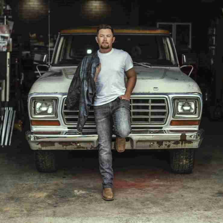 Scotty McCreery leaning on a truck