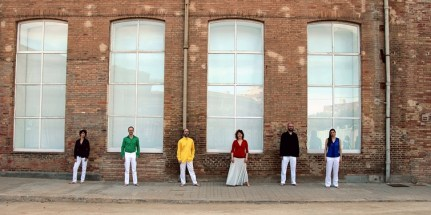 Six members of Forum Neue Vokalmusik in white trousers and coloured shirts, standing against a brick wall with large windows