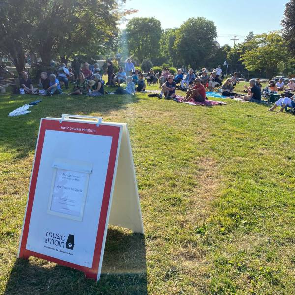 """sandwich board that says """"pop up concert with Music on Main"""" in Mount Pleasant Park with audience members sitting on the grass"""