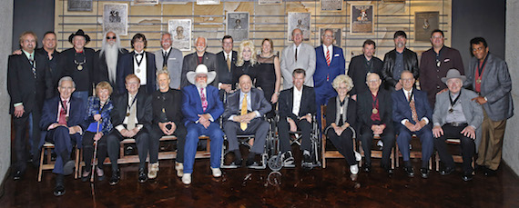 "Standing (L-R): Duane Allen, Garth Brooks, Bobby Bare, William Lee Golden, Richard Sterban, Joe Bonsall, Curtis Young, Steve Turner, Dolly Parton, CMA Chief Executive Officer Sarah Trahern, CMA Board Chairman John Esposito, Country Music Hall of Fame and Museum Director Kyle Young, Jeff Cook, Teddy Gentry, Vince Gill, and Charley Pride. Seated (L-R): Ralph Emery, Jo Walker Meador, Harold Bradley, Kris Kristofferson, Charlie Daniels, Fred Foster, Randy Travis, Brenda Lee, Charlie McCoy, E.W. ""Bud"" Wendell, and Roy Clark."